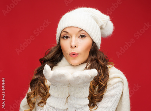 happy woman in winter clothes blowing on palms