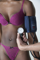 Holding a blood pressure monitor against woman