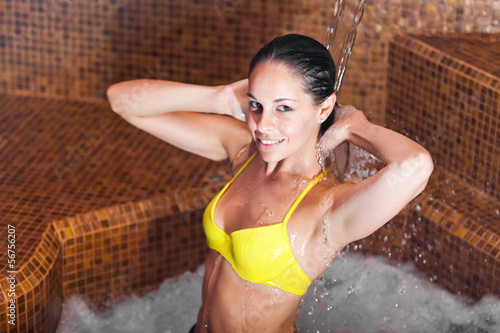 Beautiful woman taking a shower in a luxurious spa