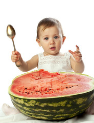baby girl with spoon near the large watermelon