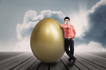 Businessman with golden egg outdoor