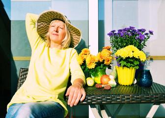 Frau nimmt ein Sonnenbad auf dem Balkon