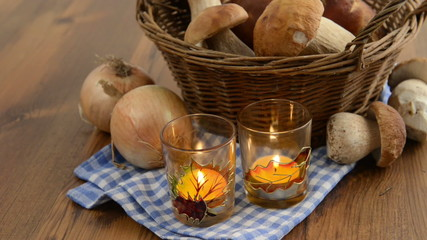 penny bun mushrooms in a basket. two burning tea light candle.