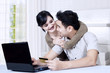Happy asian couple online shoping at home