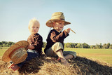 Two Children Sitting on Hay Bale in Autumn, Vintage Color