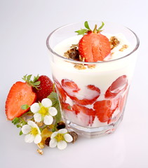 Strawberry with yogurt in glass, cereal and flowers