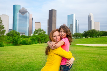 Mother and daughter happy hug in park at city skyline