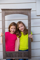 Twin sister girls posing with aged wooden border frame
