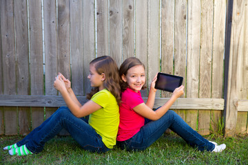 Twin sister girls playing tablet pc sitting on backyard lawn