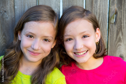 Happy twin sisters smiling on wood backyard fence