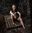 Fashionable male model sitting on grungy wooden boards