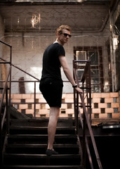 fashionable man in black standing on stairs