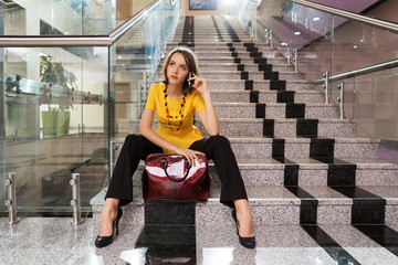 Young business woman calling on the phone in office interior