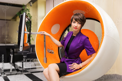 Young woman sitting on computer chair in office