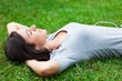 Woman listening music while relaxing on the grass