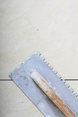 building work tool dirty trowel on new tile floor surface
