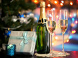 Glasses of champagne and gifts on bright background