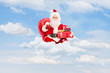 Santa Claus holding a bag full of presents on clouds