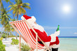 Santa Claus on a chair and drinking beer, enjoying on a beach