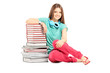 Female student with headphones sitting near a pile of books