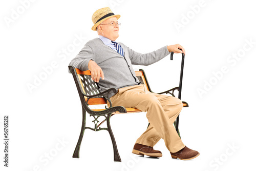 Relaxed senior man sitting on a wooden bench and thinking
