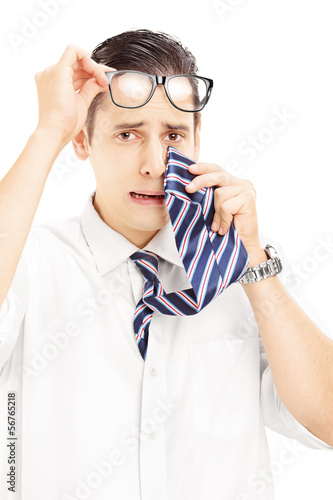 Sad young male wiping his eye from crying with a tie