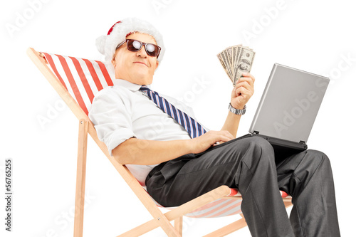 Senior man with santa hat on a chair holding banknotes and pc