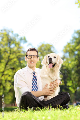 Smiling male sitting on a grass and hugging his dog in a park