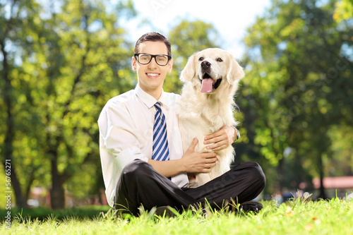 Smiling male with glasses sitting on a grass and hugging his dog