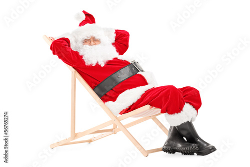 Smiling Santa Claus on a beach chair looking at camera