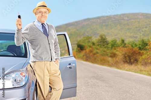 Smiling senior male holding a car key next to his automobile