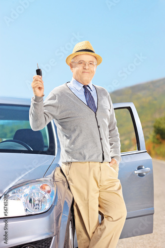 Smiling senior male holding a key next to his automobile outside
