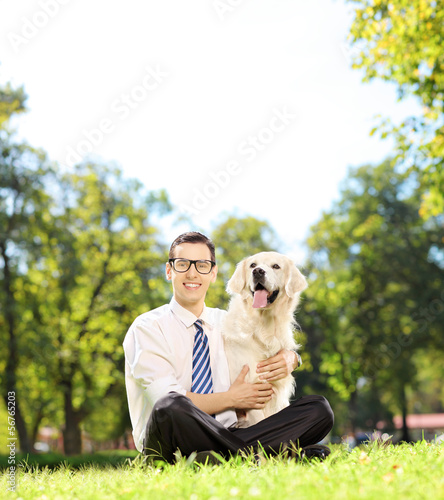 Man sitting on a grass and hugging his labrador retriever dog