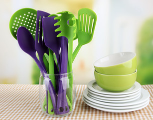 Plastic kitchen utensils in stand with clean dishes