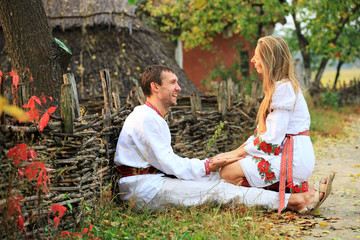 Lovely couple in Ukrainian style clothing flirting outdoors