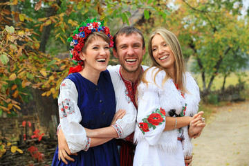 Young people in Ukrainian style clothing flirting outdoors