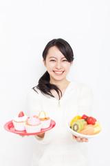 カップケーキと果物を持った女性