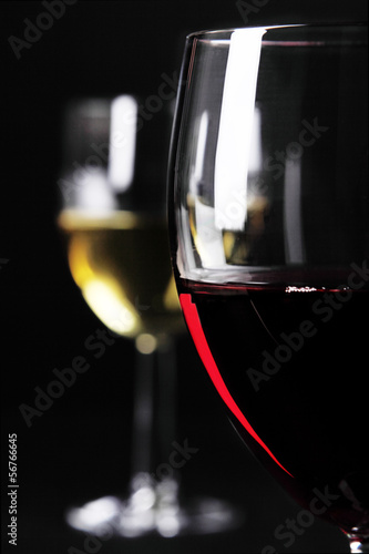 Closeup of red wine glass and white wine glass in background
