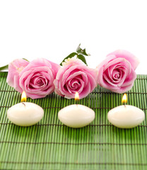 Spa composition of row rose and row candle on green mat
