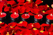 Set of red candles with rose petals in row