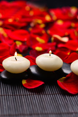 Set of stones with candle on mat with red rose petals