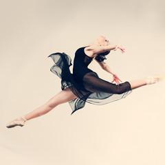Beautiful ballet-dancer posing on studio background
