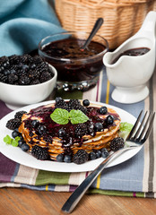 Beautiful delicious pancakes with blackberry on the table