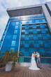 newlyweds against a blue modern building