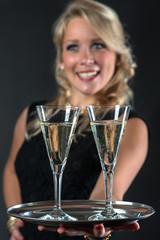 Blonde Frau hält Tablett mit Sektgläsern