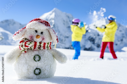 Ski, skiers with snowman enjoying winter