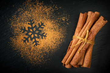 Cinnamon sticks and cinnamon powder on the chalkboard