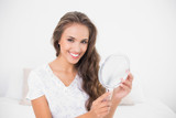 Smiling attractive brunette holding mirror