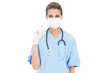 Cute brown haired nurse in blue scrubs wearing a protective mask