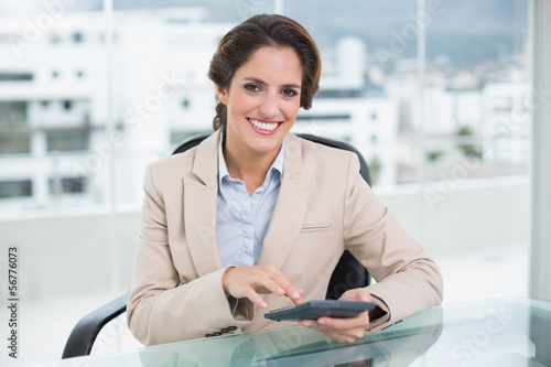 Smiling businesswoman using calculator